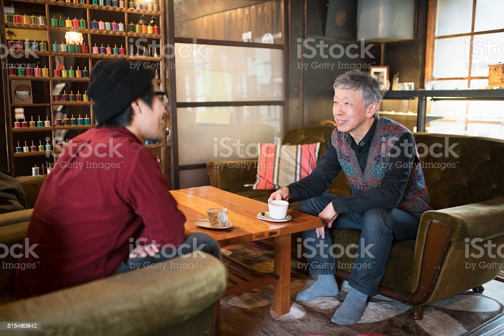 Two men talking over coffee stock photo