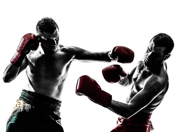 Two men Thai boxing, one punching stock photo