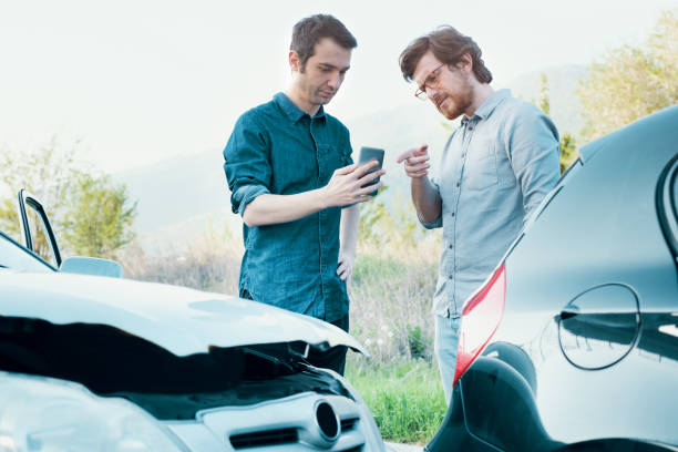 two men trying to find an agreement after a car accident - car accident stock photos and pictures