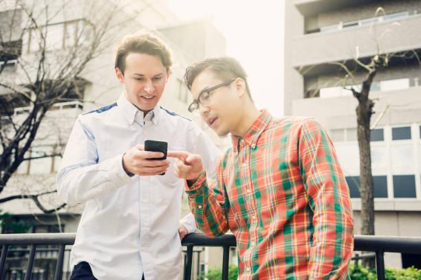 2 人の男性が市にスマート フォンを使用して ストックフォト