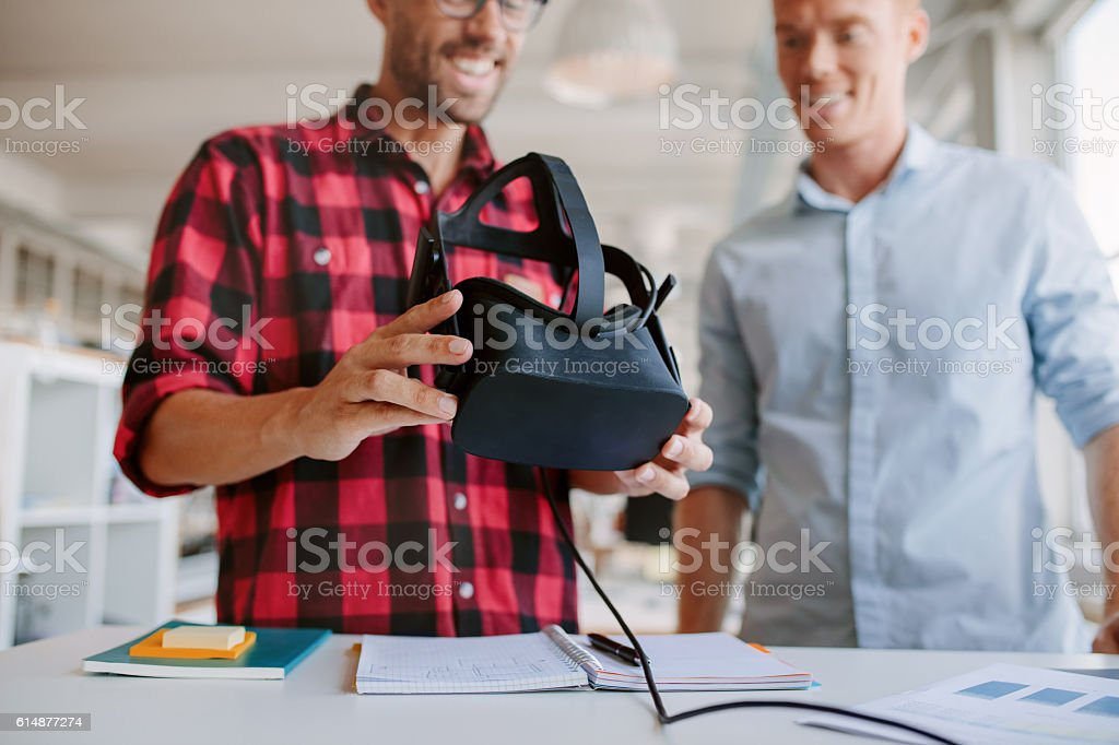 Two men using virtual reality goggles in office stock photo