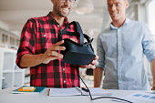 Two men using virtual reality goggles in office