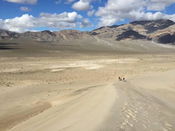 Two men walk along a sand dune at Eureka Dunes stock photo