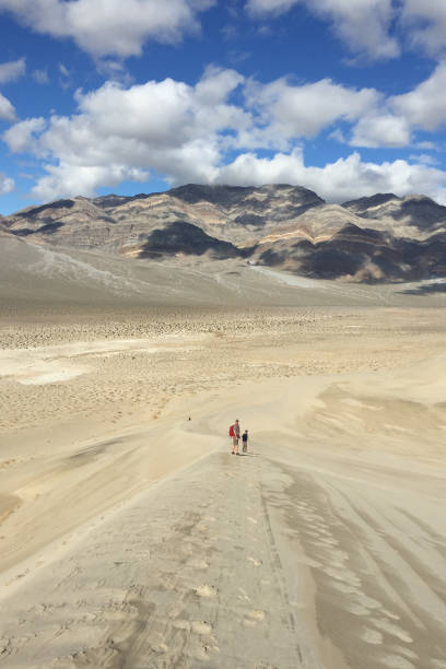 Two men walking along a sand dune at Eureka Dunes in Death Valley stock photo