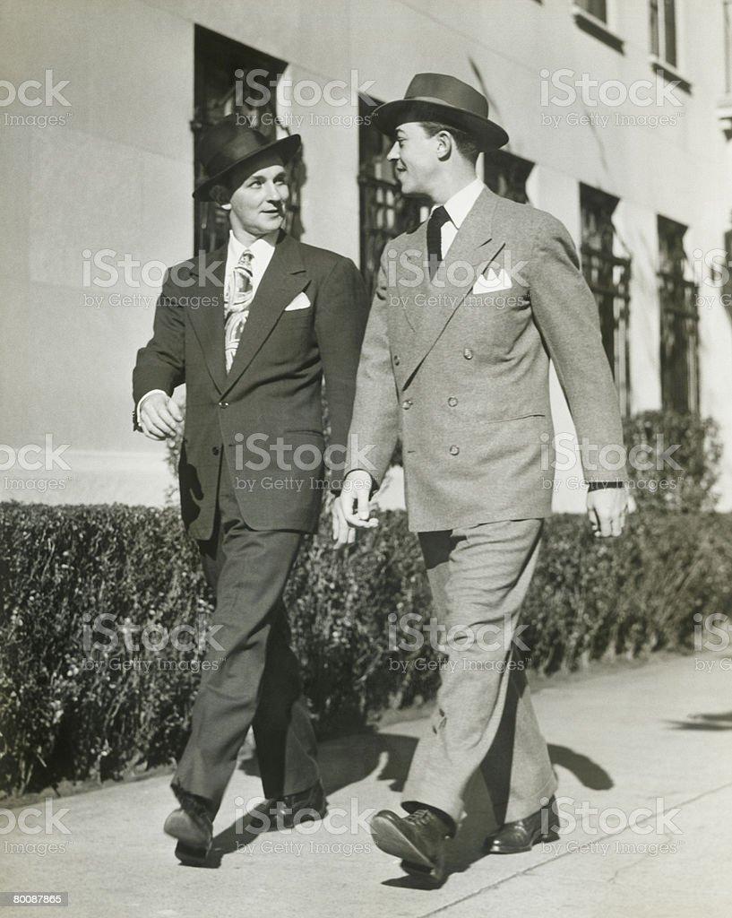 Two men walking along sidewalk 免版稅 stock photo