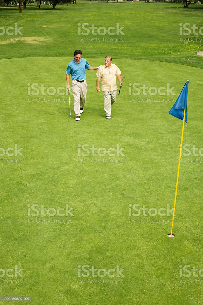 Two men walking on green royalty-free stock photo