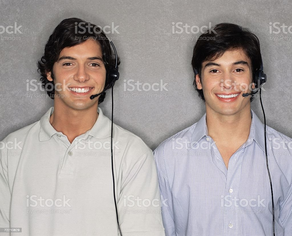 Two men wearing telephone headsets royalty-free stock photo