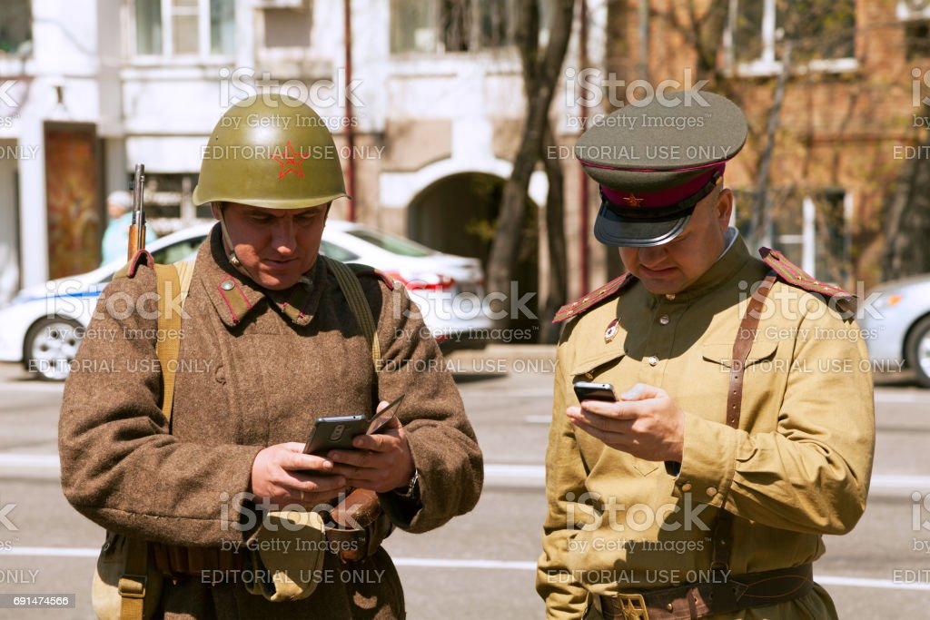 Two men wearing vintage military uniform, texting on smartphones stock photo