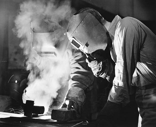 Two men welding, holding protective masks, (B&W)  20th century stock pictures, royalty-free photos & images