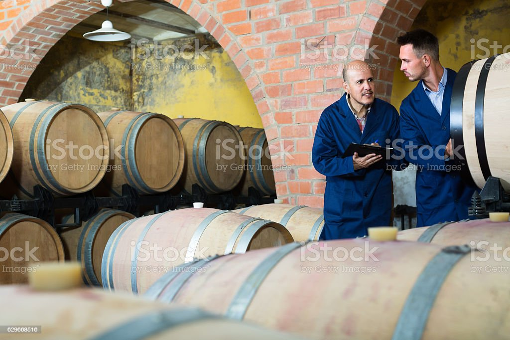 Two men winery employees writing note stock photo