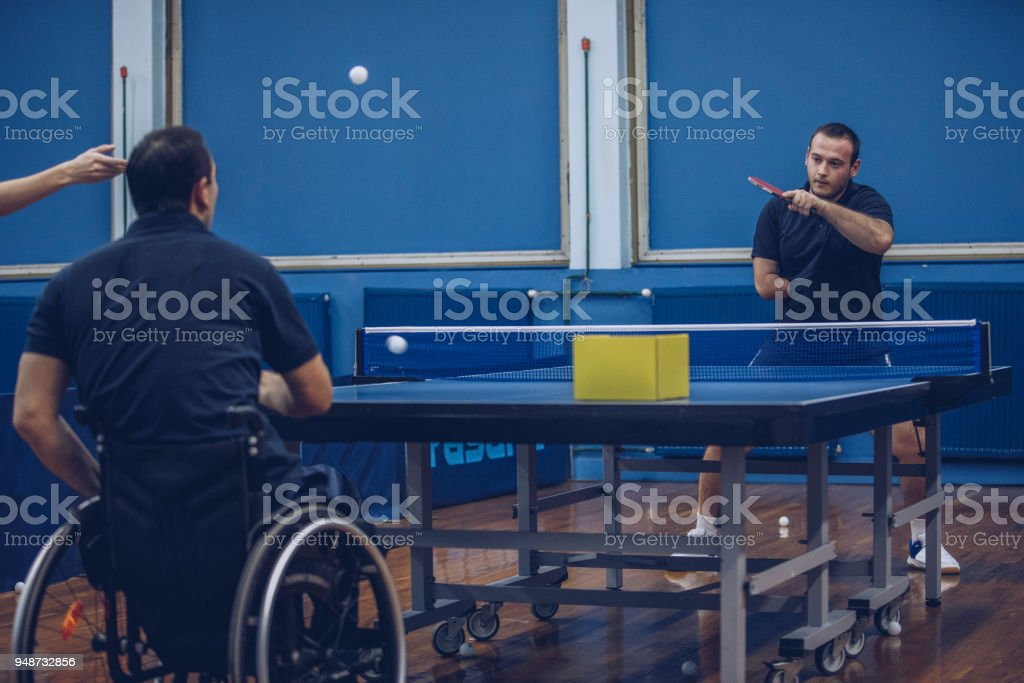Two men with differing abilities playing table tennis stock photo