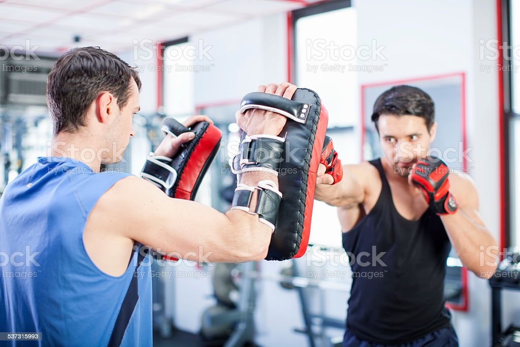 Two men working out punches in gym stock photo