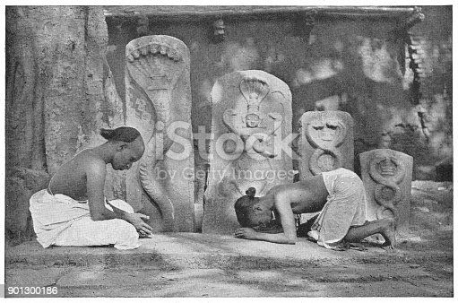 Two men worshiping on the street in Colombo, British Ceylon during the british era. Vintage photo printed in halftone circa late 19th century. Colombo is now a part of Sri Lanka.