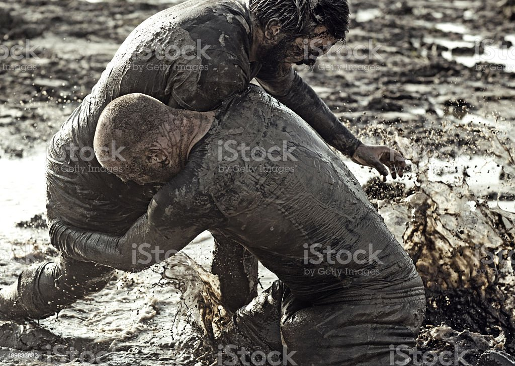 Two men wrestling in mud stock photo