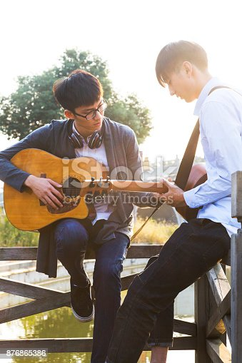 istock two men,friends playing guitar on wooden railing of bridge 876865386
