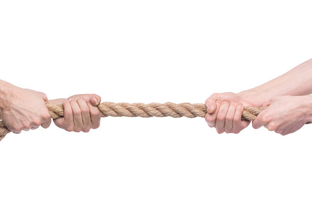Two men's hands pulling opposite ends of rope Two people pulling a rope in opposite direction isolated on white background. pulling stock pictures, royalty-free photos & images