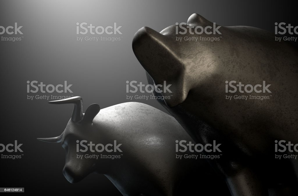 Two metal castings depicting a stylized bull alongside a bear in dramatic light representing  financial market trends stock photo