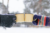 istock Two metal cups with hot tea in hands man's and woman's on a background of winter forest. 1182139485