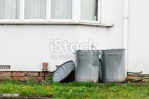 istock Two metal dustbins outside a house 940041960