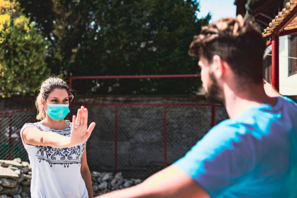 Two meters distance,please Woman wearing pollution mask and gesturing two meters distance for safety. They are outside. avoidance stock pictures, royalty-free photos & images