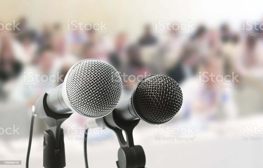 Two microphones await a speaker at meeting in auditorium royalty-free stock photo
