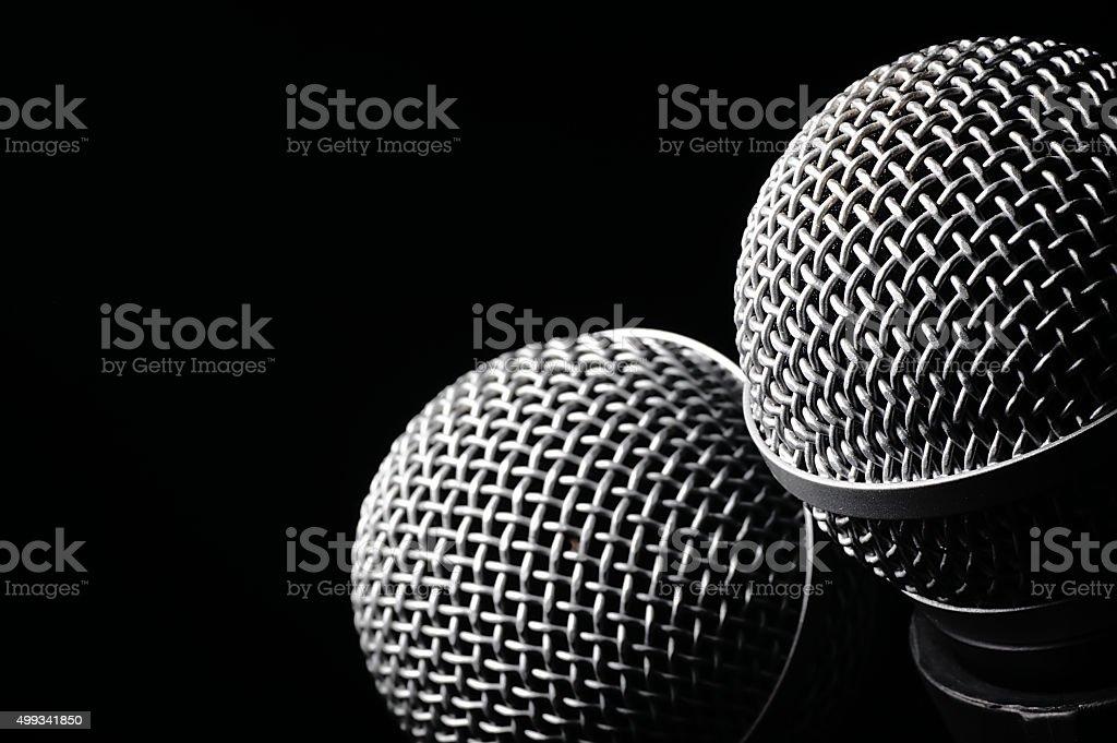 Dwa mikrofony na czarnym tle. – zdjęcie