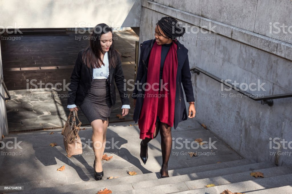 Two mid adult businesswomen walking in the city stock photo