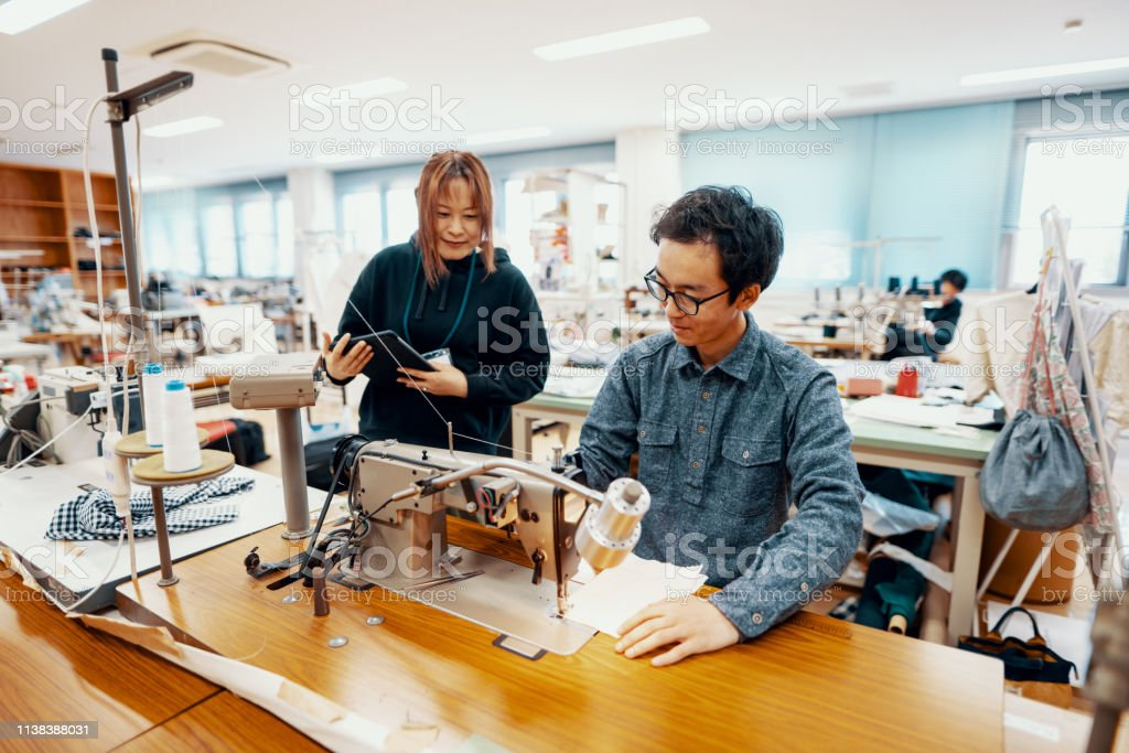 Two mid adult design professionals working together in a textile...