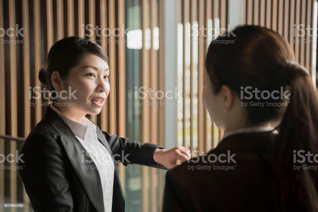 Two mid adult Japanese businesswomen in conversation, portrait stock photo