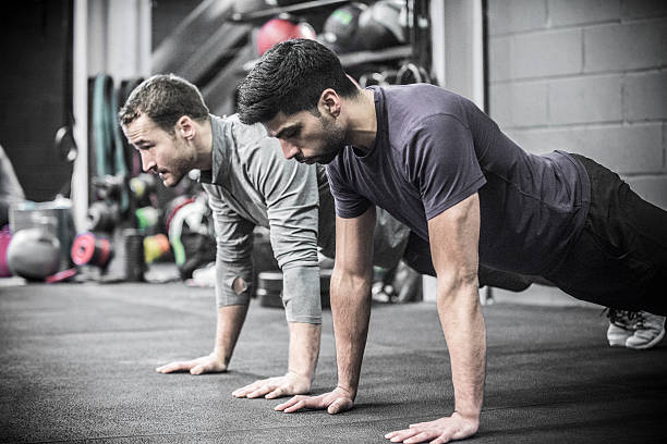 two mid adult men doing high planks in gym. - push up stock photos and pictures