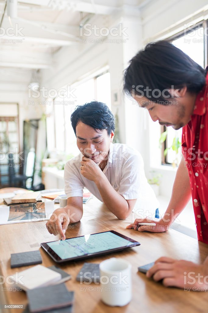 Two mid adult men lookin at a digital tablet stock photo