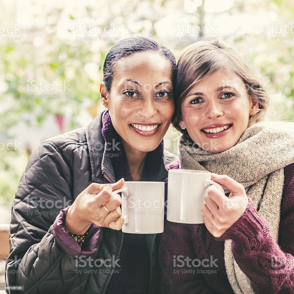 Two Mid Adult Women Toasting with Warm Coffee royalty-free stock photo