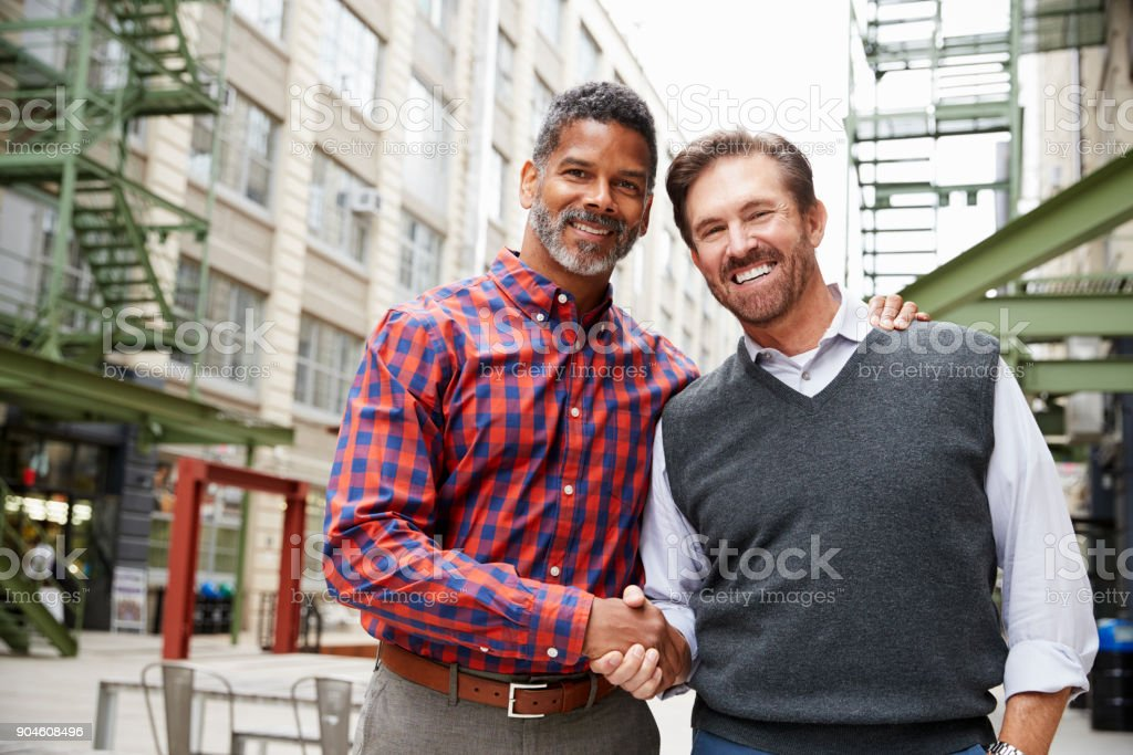 Two middle aged men shaking hands outside their workplace stock photo