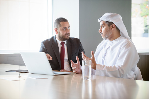 Mid adult ethnic Arab businessman with mature male colleague wearing traditional clothing. Two male adult men using laptop. Mature Arabic businessman wearing Thobe or Kandura and Ghoutra headdress explaining.