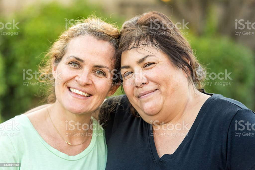 Two middle-aged women posing smiling stock photo