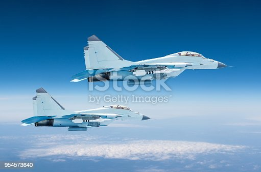 istock Two military fighters jet aircraft at high altitude, combat mission operation flying high in the sky. 954573640