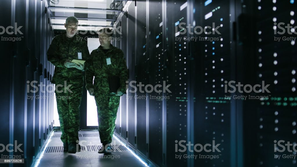 Two Military Men Walking in Data Center Corridor. One Uses Tablet Computer, They Have Discussion. Rows of Working Data Servers by their Sides. stock photo