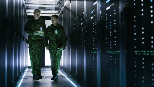 two military men walking in data center corridor. one uses tablet computer, they have discussion. rows of working data servers by their sides. - armed forces stock photos and pictures
