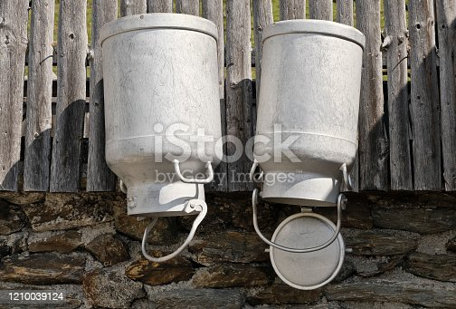 Metal cans are hung up to dry, these milk cans are used to transport milk. Typical motif in the Tyrolean mountains