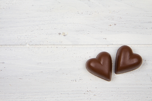 Two milk chocolate hearts on white wooden background. Valentine's Day