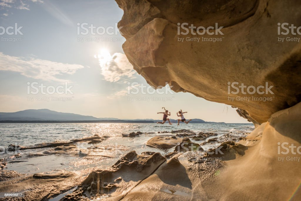 Two Millenial Sisters Jumping on Wilderness Beach Near Sandstone Formations stock photo