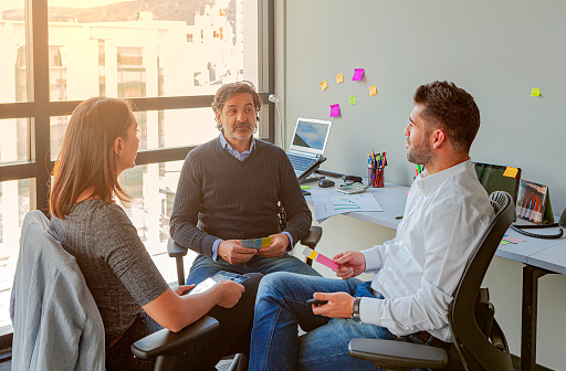 Two Millennial Generation Latin American White Collar Workers Dressed In Casual Clothes Have An Impromptu Meeting With Their Manager In A Small Office