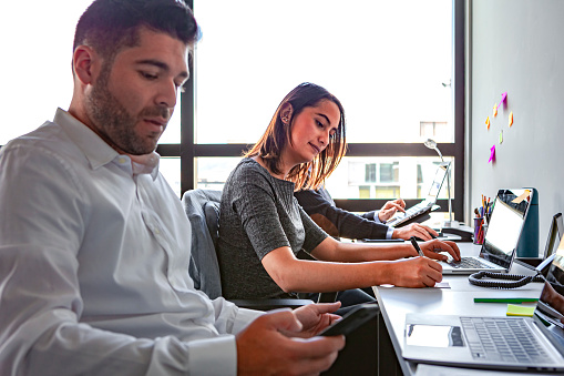 Two Millennial Generation White Collar Workers Are Seen Working At Their Desks In Their Office On A Bright Afternoon; Outside, It Is A Bright Sunny Day On The Andes
