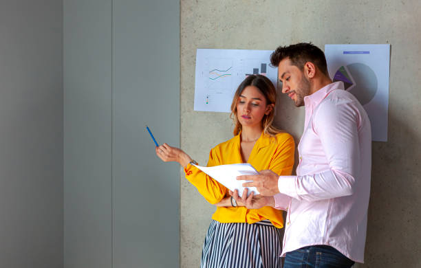 Two Millennial Generation White Collar Workers Discuss Some Data At Work; The Lady Does Not Seem To Be Very Enthusiastic About Her Assignment. Her Colleague Is Trying To Convince Her To Complete The Task stock photo
