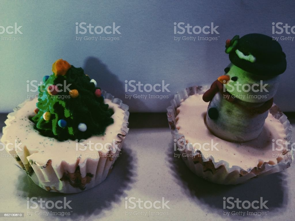 Two Mini Cupcake With A Miniature Of An Snowman And A Christmas Tree