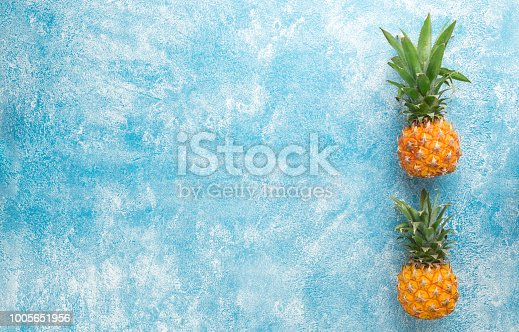 Two juicy fresh mini pineapple on a blue background, top view, space for text, long wide banner