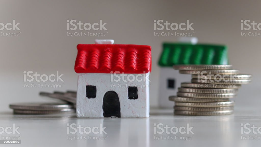 Two miniature house and pile of coins on the soft background stock photo