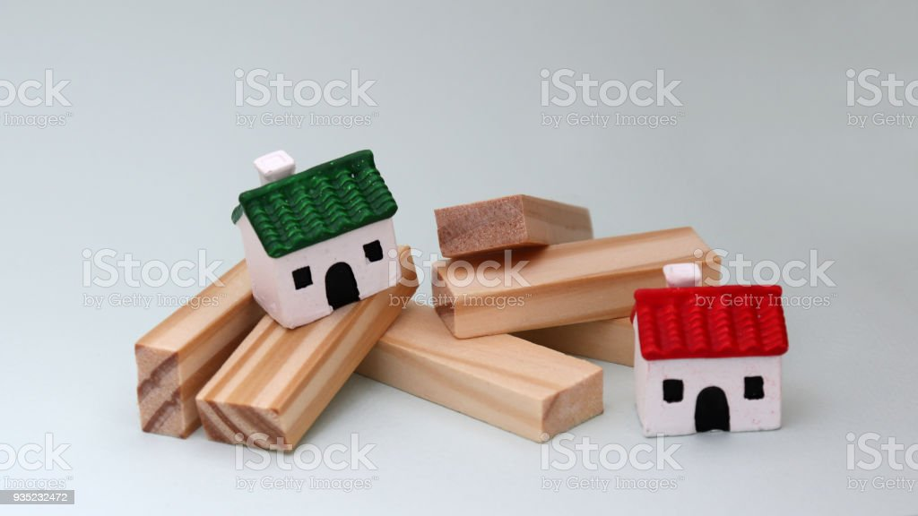 Two miniature houses and wooden blocks. stock photo