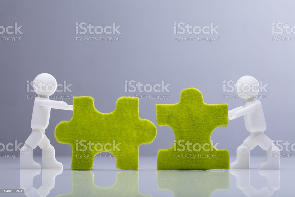 Two Miniature Human Figures Solving Green Jigsaw Puzzles stock photo