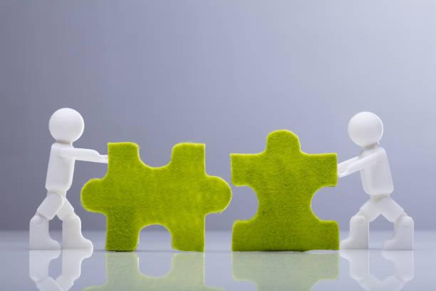 zwei menschliche figuren, die miniatur grün jigsaw puzzle lösen - fusionen und übernahmen stock-fotos und bilder